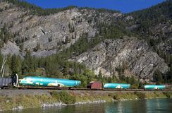 Three airplane fuselages ride the flat cars of a freight train. In Montana along the Clark Fork River Stock Photos