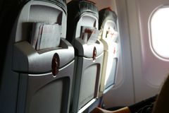 Three airplane seats with promotional brochures in aircraft passenger cabin. Light from porthole. People in chair.  Stock Photos