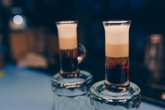 Three alcohol booze shooter layered cocktails on aB-52 - layered cocktail of three liqueurs at black background. Barman is making royalty free stock image