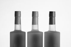 Three alcohol bottle tops in black and white. With a white background Royalty Free Stock Images