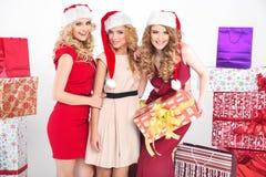 Three alluring women wearing Christmas hats Royalty Free Stock Photos