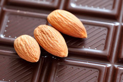 Three almonds on chocolate background. Close-up Stock Image