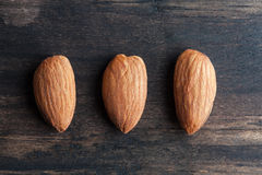 Three almonds on wooden table closup Stock Photography