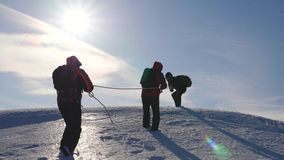 Three Alpenists climb rope on snowy mountain. Tourists work together as team shaking heights overcoming difficulties. Silhouettes of travelers rise to their royalty free stock photography