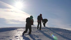 Three Alpenists climb rope on snowy mountain. Tourists work together as team shaking heights overcoming difficulties. Silhouettes of travelers rise to their stock image