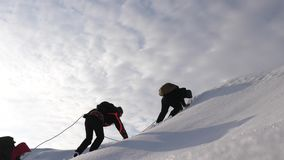 Three Alpenists in winter climb rope on mountain. Travelers climb rope to their victory through snow uphill in a strong stock video
