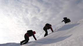 Three Alpenists in winter climb rope on mountain. Travelers climb rope to their victory through snow uphill in a strong. Three Alpenists in winter climb rope on stock photo