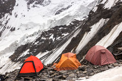 Three Alpine Tents Settled on Edge of Abyss. Mountain Climbers Camp on Rock Moraine of Glacier High Altitude Severe Landscape Royalty Free Stock Photos