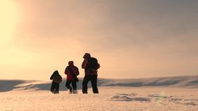 Three alpinist tourists follow each other in the snowy desert. Team work and victory. Team of business people go to. Three alpinist tourists follow each other in stock video footage