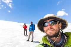 Three alpinists friends walking climbing ice glacier mountain An. Alpinists mountaineers tourists friends walking climbing ice mountain glacier tied rope Stock Photo