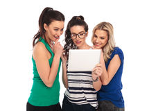 Three amazed  women looking at the screen of a tablet Stock Photos