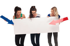 Three amazed women pointing arrows to a big blank board Stock Image