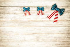 Three American Flag Bows on Rustic Wood Board Background with room or space for copy, text.  Horizontal, sepia processing. Horizontal wood slat, plank boards Royalty Free Stock Image