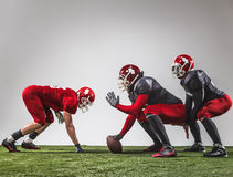 The three american football players in action. On green grass and gray background Royalty Free Stock Photography