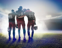 The three american football players on on stadium background. The back view of three caucasian fitness men as american football players on stadium background Stock Image