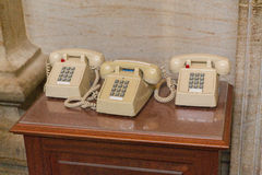 Three American push button fixed telephones. Old style classic amercian telephones - three of them on one desk Royalty Free Stock Images