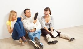 Three amused friends with books. Three kidding students with books - one man and two women stock images