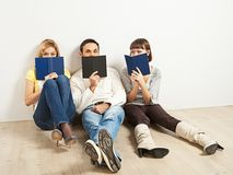 Three amused friends with books. Three kidding students with books - one man and two women royalty free stock photos