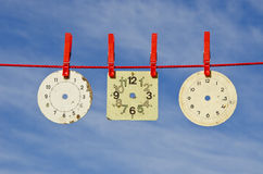 Three ancient clock dial on red string Stock Photos