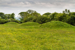 Three ancient tumuli, barrows or burial mounds. Royalty Free Stock Photos