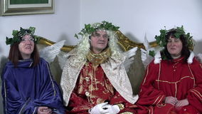 Three angels sit and look around with laurels on their heads. Three old angels in baroquesque clothes sit on a couch stock footage