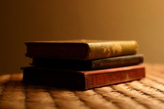 Three antique books. Stacked on side table stock photo