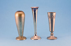 Three antique metal silver goblet cup on blue background Royalty Free Stock Photos