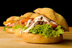 Three appetizing burgers on wooden table Stock Photography