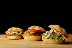 Three appetizing burgers on wooden table Stock Images