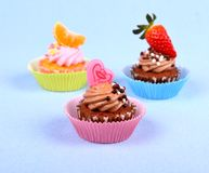 Three appetizing cupcakes with heart, tangerine, and strawberry Royalty Free Stock Photo