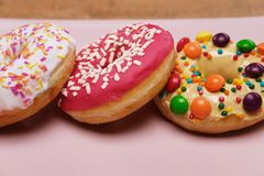 Three appetizing donuts lie on a pink ceramic plate. stock photos