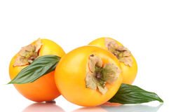 Three Appetizing Persimmons With Green Leaves Royalty Free Stock Photo
