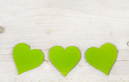 Three apple green hearts on white shabby style wooden background Royalty Free Stock Images