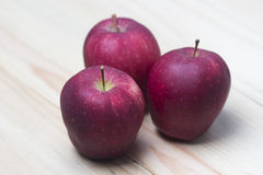 Three apple on a wooden table. Red apple on wooden background stock photography