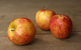 Three apples. Appless on wooden background. One is in focus two are defocused Stock Images