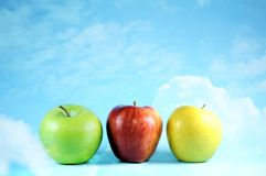 Three apples on bright sky and clouds. Stock Photo