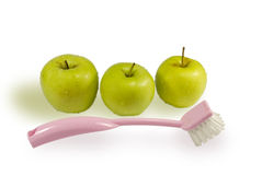 Three apples and brush for washing of fruit. Three wet green apples and pink brush for washing of fruit. On a white background Royalty Free Stock Photo