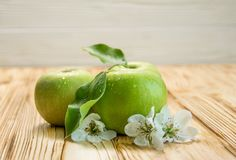 Three apples with flowers. On a wooden brown background Royalty Free Stock Photos