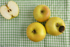 Three apples and half. On green checkered tablecloth Stock Images