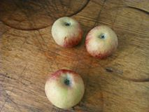 Three apples on a old, shabby and scruffy kitchen wooden surface. Unique image. stock images