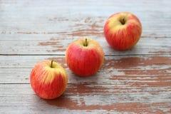 Three apples on a wood table, diagonal row. Three apples on an old wood table, lying in a diagonal row royalty free stock photos
