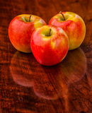 Three Apples on an Old Wooden Table. Studio shot of three fresh apples on an old wooden table Stock Image