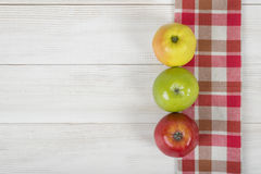 Three apples placed on red checkered kitchen tablecloth. Top view. Three colored whole apples placed on red checkered kitchen tablecloth. Top view Stock Photos