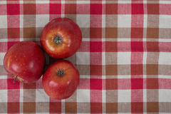 Three apples placed on red checkered kitchen tablecloth. Top view. Three red whole apples placed on red checkered kitchen tablecloth. Top view Stock Photo