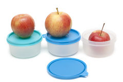 Three apples and plastic containers Stock Photo