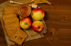Three apples, slices of rye bread, honey, wheat ears on sacking Stock Image