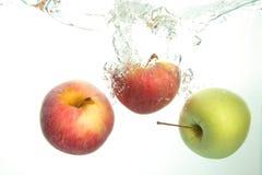Three Apples splash in water on white stock photos