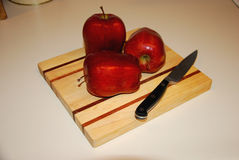 Three apples on wooden cutting board Royalty Free Stock Image