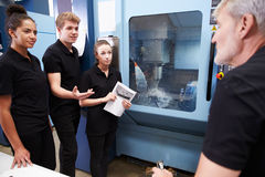 Three Apprentices Working With Engineer On CNC Machinery Royalty Free Stock Photography