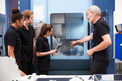 Three Apprentices Working With Engineer On CNC Machinery Stock Image